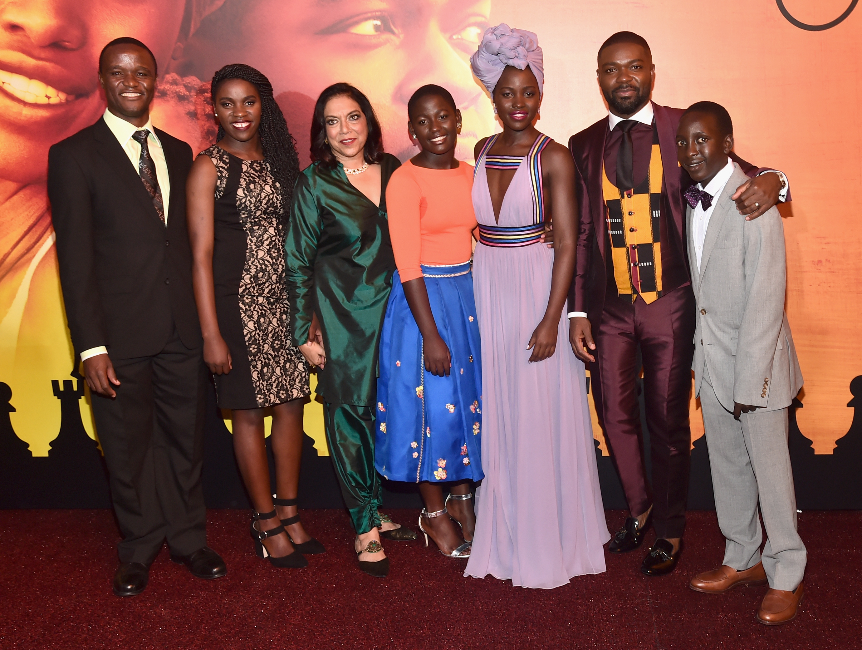 "HOLLYWOOD, CA - SEPTEMBER 20: (L-R) Chess Coach and Director of Sports Outreach in Uganda, Robert Katende, Ugandan national chess champion Phiona Mutesi, Director Mira Nair, actors Madina Nalwanga, Lupita Nyong'o, David Oyelowo and Martin Kabanza arrive at the U.S. premiere of Disney's ""Queen of Katwe"" at the El Capitan Theatre in Hollywood. The film, starring David Oyelowo, Oscar winner Lupita Nyong'o and newcomer Madina Nalwanga, is directed by Mira Nair and opens in U.S. theaters in limited release on September 23, expanding wide September 30, 2016. On September 20, 2016 in Hollywood, California. (Photo by Alberto E. Rodriguez/Getty Images for Disney) *** Local Caption *** Robert Katende; Phiona Mutesi; Mira Nair; Madina Nalwanga; Lupita Nyong'o; David Oyelowo; Martin Kabanza"